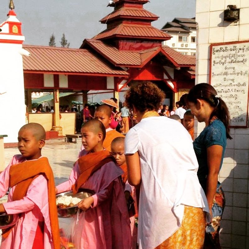 Remise d'offrandes à de jeunes filles bouddhistes lors du Nouvel An à Inle Lake au Myanmar